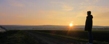 Ein Jugendlicher schaut in den Sonnenuntergang.